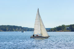Sailboat, river and islands. Sailboat with white canvas floating along the shore. Swedish archipelago. Summer season Stock Images