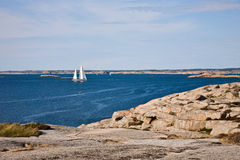 Sailboat and rocky coast Royalty Free Stock Photos