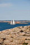 Sailboat and rocky coast Royalty Free Stock Photography