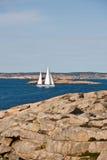 Sailboat and rocky coast Royalty Free Stock Photography
