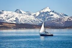 Sailboat and rocky coast Stock Image