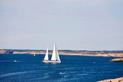 Sailboat and rocky coast Stock Photo