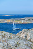 Sailboat in the rocky coast Stock Image