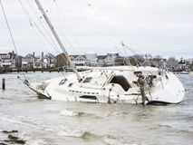 A sailboat run aground after breaking free of its moorings. After a storm a sailboat broke free from its moorings and ran aground on a Nantucket beach royalty free stock image
