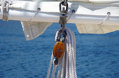 Sailboat sail and wooden rigging ropes against water background Stock Photography