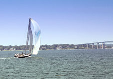 Sailboat. Sailing alongshore towards bridge stock photo