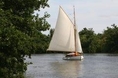 Sailboat sailing home. A boat tacks through the Norfolk Broads royalty free stock photography