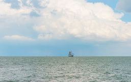 Sailboat sailing in a lake. Below a cloudy sky Stock Images