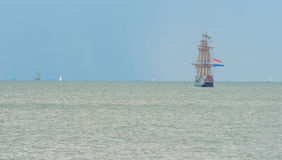 Sailboat sailing in a lake. Below a cloudy sky Royalty Free Stock Photo