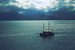 Sailboat Sailing Near Mountains Under Cloudy Sky Stock Photo