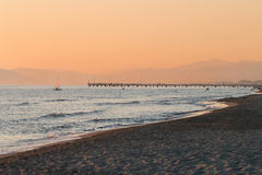 Sailboat sailing next to Forte dei Marmi's pier at sunset Royalty Free Stock Photography