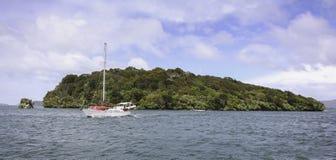 Sailboat sailing past Stewart Island, New Zealand Stock Photos