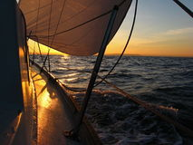 Sailboat sailing at sunrise. Watching a sunrise while under sail sailing in the Puget Sound Royalty Free Stock Photos