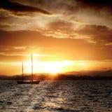 Sailboat sailing by sunset. Detail of sailboat sailing at Santander bay by sunset (Spain Stock Images