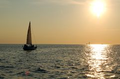 Sailboat sailing to sunset. Sailboat sailing into the sea right to the sun Royalty Free Stock Images