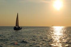 Sailboat sailing to sunset Royalty Free Stock Images