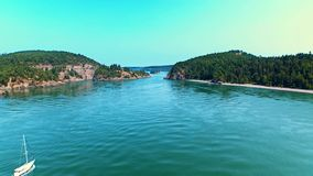 Sailboat sailing towards a bridge by oceanfront bay on a sunny day. Breathtaking aerial of a sailboat sailing towards an ocean bay bridge between cliff rocks on stock video footage