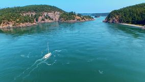 Sailboat sailing towards a bridge by oceanfront bay on a sunny day. Breathtaking aerial of a sailboat sailing towards an ocean bay bridge between cliff rocks on stock video