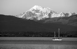 Sailboat Sails Down Motoring Puget Sound Mt Baker Cascade Range. A boat travels the water at sunset in Puget Sound Washington Stock Photos