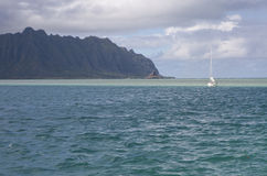 Sailboat by the sandbar in Kaneohe Bay, Hawaii. Landscape view of the sandbar in Kaneohe Bay, Oahu, Hawaii, with a sailboat and the Ko'olau mountain range in the Stock Photo