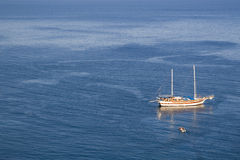 Sailboat in sea. Sailboat on calm sea with lowered sails shot from above, with copyspace Royalty Free Stock Photography