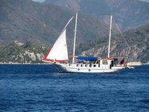 Sailboat in the sea on a background of forested mountains Royalty Free Stock Photos