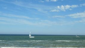 Sailboat in the sea in the clear weather, on sky with a few white clouds background. Sailing yacht in the blue sea near the coast. stock footage