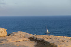 Sailboat in the sea. A panoramic view of the ocean with a blue sailboat at the bottom right Stock Image