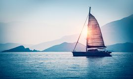 Sailboat in the sea. In the evening sunlight over beautiful big mountains background, luxury summer adventure, active vacation in Mediterranean sea, Turkey Royalty Free Stock Photography