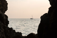 Sailboat at the sea, view from a dark cave Royalty Free Stock Image