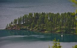 Sailboat in secluded bay on alpine lake stock photos