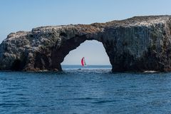 Sailboat framed byArch Rock on Anacapa Island Royalty Free Stock Photography