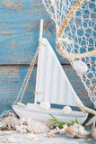 Sailboat with shells and fishing net on blue background for holi Stock Photos