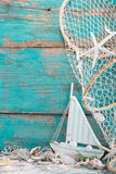 Sailboat with shells and fishing net on turquoise background for royalty free stock photography
