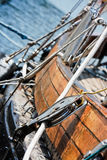 Sailboat side. Side of the wooden sailboat with cordage pulley and ropes, against sea background Stock Photo