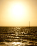 Sailboat silhouette against dramatic golden sunset over the sea Royalty Free Stock Images