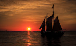 Sailboat silhouetted against sunset. Schooner sailboat sailing into the sunset silhouetted on Key West, Florida Stock Photography