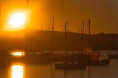 Sailboat silhouettes, magnificent golden warm sunset in Ibiza marina. Sailboats & small yachts in Ibiza marina harbour in the evening. Magnificent golden warm stock photo