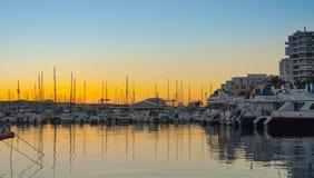 Sailboat silhouettes, magnificent golden warm sunset in Ibiza marina. Sailboats & small yachts in Ibiza marina harbour in the evening. Magnificent golden warm stock photos