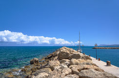 Sailboat at the stone breakwater in the harbor Stock Photos