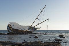 Sailing ship stranded on the rocks. Sailboat, stranded along the coast on the cliff of Sardinia in the Mediterranean Sea royalty free stock images