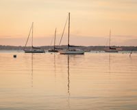Sailboat Sunrise at Anchor. These are several sailboats at anchor near Jamestown, Rhode Island in Narragansett Bay. Fort Adams is seen in the distant background stock photography