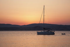 Sailboat at sunrise. With dinghy Royalty Free Stock Image