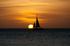 Sailboat at sunset. Image capturing the sunset at sea. A boat is sailing towards the sun. The image was taken form Palm Beach, Aruba stock photo