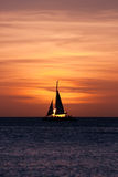 Sailboat at sunset. Image showing a sailboat on sea navigating towards the sunset. The image was taken from Palm Beach, Aruba, in the Caribbean Sea Royalty Free Stock Image