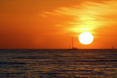 Sailboat Sunset. Sailboat on horizon at sunset with pirate ship off in distance Royalty Free Stock Photo