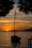 Sailboat at Sunset. A sailboat during an orange sunset stock photos