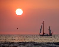 Sailboat at sunset. Sailboat returning to harbor at sunset royalty free stock photo
