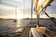 Sailboat at sunset. A fabulous sailing boat trip, among the marvels of the calm sea of Sardinia, a moment of peace admiring the magical sunset light Stock Photos