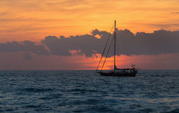 Sailboat sunset fantasy with a silhouetted boat sailing along it Royalty Free Stock Photos